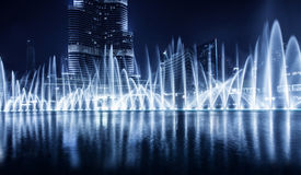 Dubai fountain. Beautiful famous fountain in Dubai at night, romantic music, water dance, blue lights, luxury resort, evening cityscape royalty free stock images
