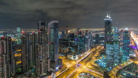 Dubai-Geschäftsbuchttürme belichtet am Nacht-timelapse Dachspitzenansicht einiger Wolkenkratzer und neuer Türme darunter stock video