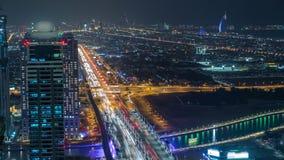 Dubai-Geschäftsbuchttürme belichtet am Nacht-timelapse Dachspitzenansicht einiger Wolkenkratzer und neuer Türme darunter stock video footage