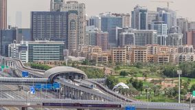 Dubai Golf Course with a cityscape of Gereens and tecom districts at the background aerial timelapse. Traffic on sheikh zayed road with junction and metro stock footage