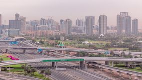 Dubai Golf Course with a cityscape of Gereens and tecom districts at the background aerial timelapse. Traffic on sheikh zayed road with junction and bridges stock video