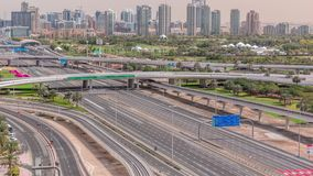 Dubai Golf Course with a cityscape of Gereens and tecom districts at the background aerial timelapse. Traffic on sheikh zayed road with junction stock footage