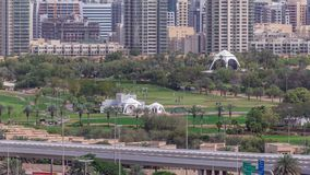 Dubai Golf Course with a cityscape of Gereens and tecom districts at the background aerial timelapse. Traffic on sheikh zayed road with junction stock video