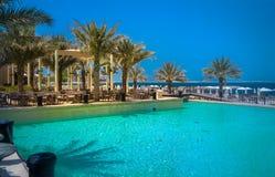Dubai. Heavenly oasis in Ras al Khaimah. The beach with sunbeds and sunshades in Dubai, on the shores of the Arabian Gulf. Toning. Stock Photos