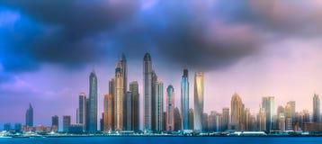 Dubai Marina bay view from Palm Jumeirah, UAE. Modern buildings of Dubai Marina bay with dramatic cloudscape on background, view from Palm Jumeirah during sunset Royalty Free Stock Photography