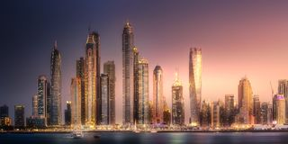 Dubai Marina bay view from Palm Jumeirah, UAE. Modern buildings with gold reflection of Dubai Marina bay view from Palm Jumeirah at sunset, UAE Royalty Free Stock Images