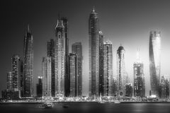 Dubai Marina bay view from Palm Jumeirah, UAE. Modern buildings with gold reflection of sunset on Dubai Marina bay view from Palm Jumeirah, UAE. . Black and Stock Photography