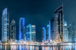 Dubai Marina bay view from Palm Jumeirah, UAE. Modern buildings of Dubai Marina bay with lights at night on background, view from Palm Jumeirah, UAE Stock Photo