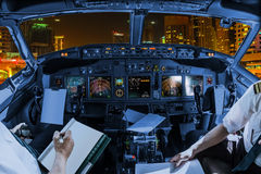 Dubai Marina Cockpit. Airplane cockpit flying on Dubai Marina by night, United Arab Emirates, with pilots arms and blank white papers for copy space Royalty Free Stock Photos