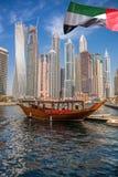 Dubai marina med fartyg mot skyskrapor i Dubai, Förenade Arabemiraten Arkivbild