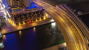 Dubai Marina at night view on river with boats and. DUBAI, UAE Dubai Marina at night view on river with boats and bridge with traffic timelapse near hotel. In stock video