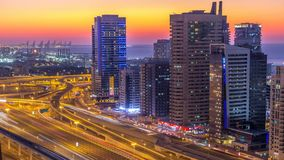 Dubai marina with traffic on sheikh zayed road panorama day to night timelapse lights turn on. Dubai marina with traffic on sheikh zayed road panorama day to stock footage