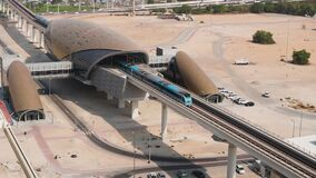 Dubai metro train departs from the station, beautiful view from above.