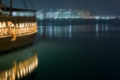 Dubai - o Dhow ilumina a reflexão e o constructi da palma imagens de stock royalty free