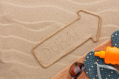 Dubai  pointer and beach accessories lying on the sand Royalty Free Stock Photography