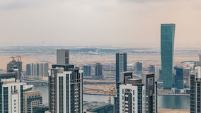 Dubai`s business bay towers before sunset timelapse. Rooftop view of some skyscrapers and new towers under construction. Cloudy sky stock footage