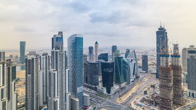 Dubai`s business bay towers before sunset timelapse. Rooftop view of some skyscrapers and new towers under construction. Traffic on road with intersection stock footage