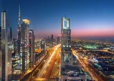 Dubai Sheikh Zayed Road vid solnedgång med gator för tung trafik Arkivbild