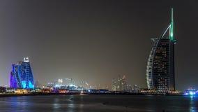 Dubai skyline with Burj Al Arab hotel at night timelapse. View from jumeirah beach. Dubai marina towers on background. Burj Al Arab is a luxury 5 stars hotel stock footage