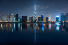 Dubai Skyline by night. Cityscape and Burj Khalifa scenic view by night and their reflection on water Stock Photos