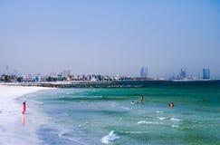 dubai Sommer 2016 Der Persische Golf mit der Linie des Strandes von Adschman Frau in den roten Spielen auf dem Strand Stockbilder