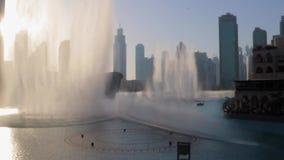 Dubai springbrunn nära Burj Khalifa som är upplyst vid staden på solnedgången stock video