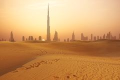 Dubai-Stadtskyline bei dem Sonnenuntergang gesehen von der Wüste stockbilder