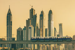 Dubai with subway and skycrapers at sunset. Royalty Free Stock Photography