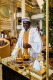 Dubai. In the summer of 2016. The hotel employee pours Arabic coffee in the hotel Park Hyatt. Abu Dhabi. The hotel employee pours Arabic coffee in the hotel Park Stock Image