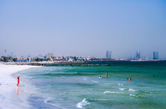 Dubai. Summer 2016. The Persian Gulf with the line of the beach from the Ajman. Woman in red plays on the beach. Stock Images