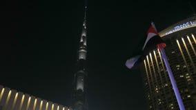 DUBAI, U A e - EN ENERO DE 2018: tiro asombroso con la torre de Burj Khalifa y edificio moderno contra el cielo nocturno oscuro almacen de metraje de vídeo