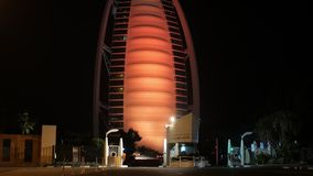 DUBAI, U.A.E. - JAN, 2018: main entrance of Burj Al Arab hotel in night, building is changing illumination. On red and yellow stock video