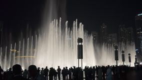 DUBAI, U.A.E. - JAN, 2018: tourists are watching amazing show of large dancing fountains in night stock video