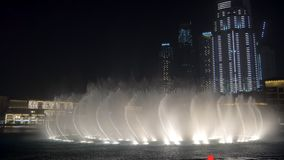 DUBAI, U.A.E. - JAN, 2018: water jets of dancing large fountains are squirming in night time near Dubai Mall stock footage