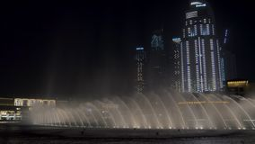DUBAI, U.A.E. - JAN, 2018: water jets and splashes of dancing large fountains are squirming in night time stock footage
