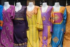 Dubai UAE är färgrika kvinnors klänningar visat till salu på den Al Naif souqen i Deira arkivfoto