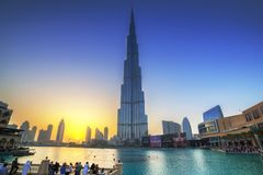 Downtown of Dubai with Burj Khalifa building at sunset. DUBAI, UAE - 1 APRIL 2014: Downtown of Dubai with Burj Khalifa building at sunset, UAE. Dubai is the most Stock Photos