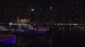 Night view of the harbor with yachts in the expensive tourist area Dubai Marina stock footage video. Dubai, UAE - April 01, 2018: Night view of the harbor with stock footage