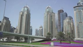Travel on the roads of Dubai, skyscrapers of the Dubai Marina area, view from the car window stock footage video. Dubai, UAE - April 01, 2018: Travel on the stock video footage