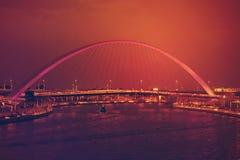 DUBAI UAE - 12 DE FEVEREIRO DE 2017: Arqueie a ponte pedestre sobre o canal da água de Dubai iluminado na noite Emiratos Árabes U Fotos de Stock Royalty Free