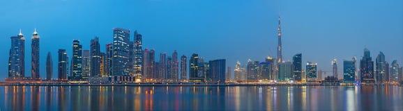 DUBAI, UAE - 23 DE MARÇO DE 2017: O panorama da noite sobre o canal novo com a baixa e Burj Khalifa elevam-se Foto de Stock