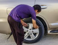 A man working with a car wheel royalty free stock images