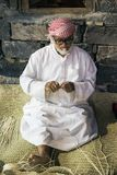 The old man is weaving straw hats to meet guests in the pavilio. DUBAI, UAE - DECEMBER 4, 2017: The old man is weaving straw hats to meet guests in the pavilion stock image