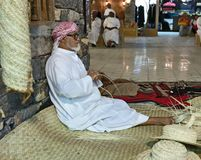 The old man is weaving straw hats to meet guests in the pavilio. DUBAI, UAE - DECEMBER 4, 2017: The old man is weaving straw hats to meet guests in the pavilion stock photography