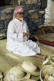 The old man is weaving straw hats to meet guests in the pavilio. DUBAI, UAE - DECEMBER 4, 2017: The old man is weaving straw hats to meet guests in the pavilion royalty free stock images