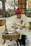 Shoemaker artisan in national clothes in the pavilion of Turkey. DUBAI, UAE - DECEMBER 4, 2017: Shoemaker artisan in national clothes in the pavilion of Turkey royalty free stock photo