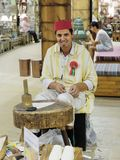 Shoemaker artisan in national clothes in the pavilion of Turkey. DUBAI, UAE - DECEMBER 4, 2017: Shoemaker artisan in national clothes in the pavilion of Turkey royalty free stock image