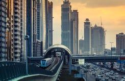 DUBAI, UAE - 16. DEZEMBER 2015: Dubai-` s im Stadtzentrum gelegene Architektur am Abend mit dem Metroeinschienenbahnzug, der zu d Stockfotos