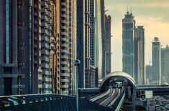 DUBAI, UAE - 16. DEZEMBER 2015: Moderne Architektur Dubais bei Sonnenuntergang mit einer Metrostation Stockfoto