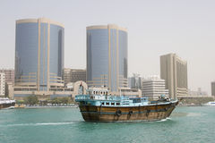 Dubai UAE A dhow old wooden sailing vessel cruises down Dubai Creek in front of the Rolex Tower. Royalty Free Stock Images